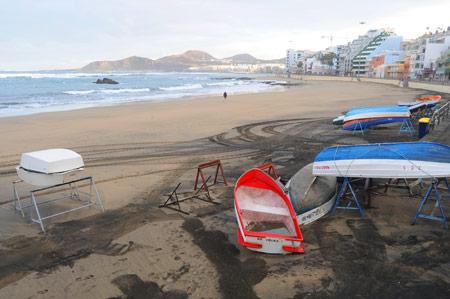 La marea cabreada barre los botes de la playa.