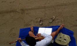 Acariciando la guitarra a la orilla del mar.