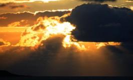 El sol cae entre nubes.
