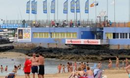 La playa se divierte bajo el anuncio de la celebración del 30º aniversario de Belén María, un símbolo para La Isleta y los estibadores canarios.