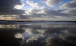 Reflejos de ocaso en arena negra.