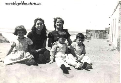 Dora Suárez, Olga y Nora Santana, Juan Ambrosio en 1954. Sentados sobre una duna de arena, atrás se ve lo que actualmente es la C/ Portugal- colecc. Elena Santana Auyanet.