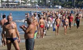 Cayetano, en primer termino, de palique en un domingo de playa abarrotado de gente.