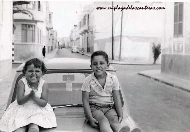 Margarita  Artiles con su hermano Rafael sobre un coche en la esquina de las calles Luis Morote y Bernardo de La Torre,  sobre 1960.  Familia Artiles Ramírez
