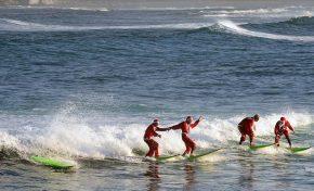 Los Papás Noel hacen surf en Las Canteras
