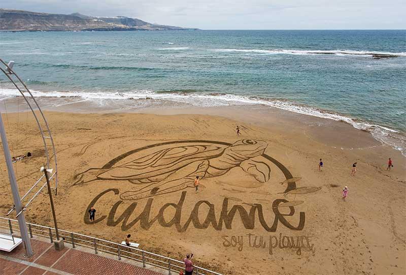 Se dibuja en la arena una enorme tortuga para celebrar la llegada del verano. «Time-lapse»